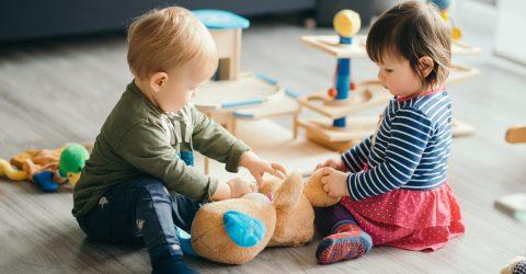 Deux enfants jouant assis par terre.