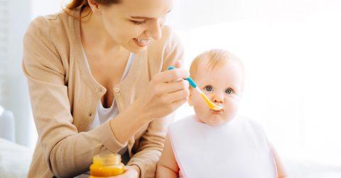 Assistante maternelle nourrissant un bébé.