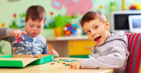 Enfants en situation de handicap jouant autour d'une table.