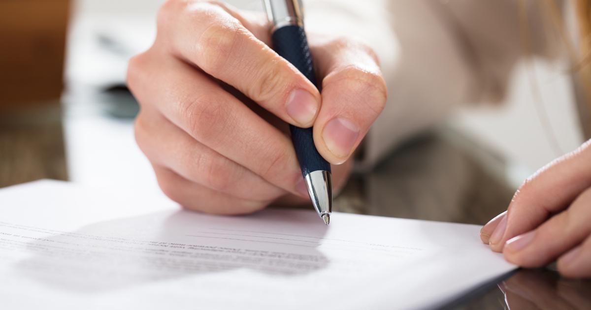 Gros plan sur une main tenant un stylo et remplissant un formulaire.