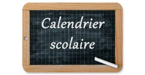 Ardoise sur laquelle est écrit calendrier scolaire.