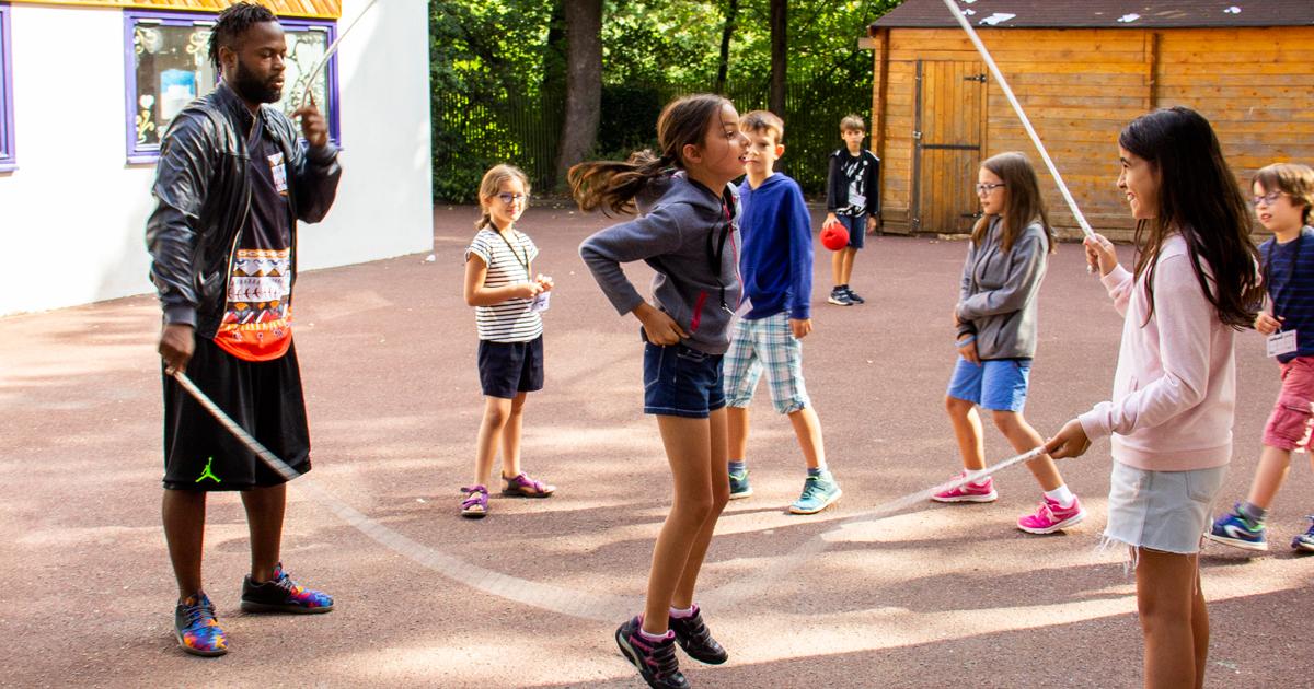Enfants jouant à la corde à sauter avec un animateur.
