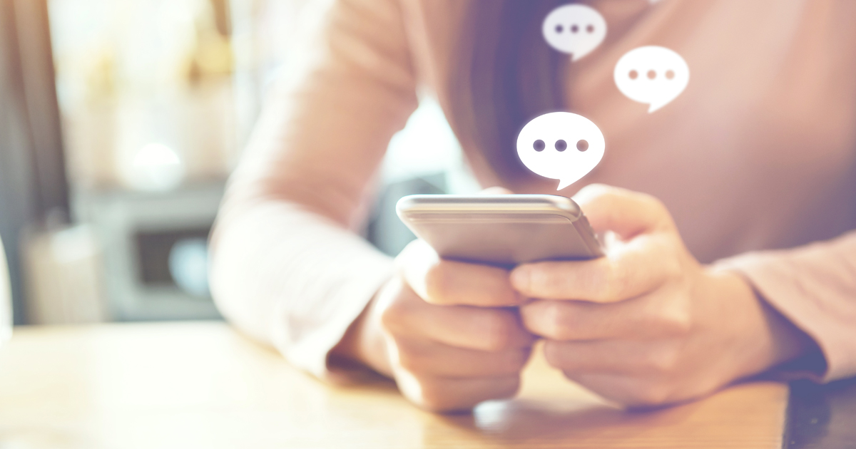 Mains tenant un téléphone portable surmonté de bulles de discussion fictives.