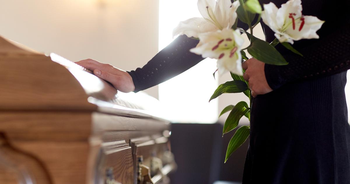 Personne tenant un bouquet de lys et posant une main sur un cercueil.