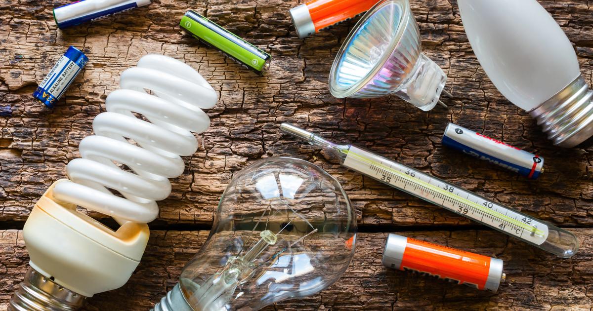 Ensemble de déchets éparses, ampoules, piles, posés sur une table.