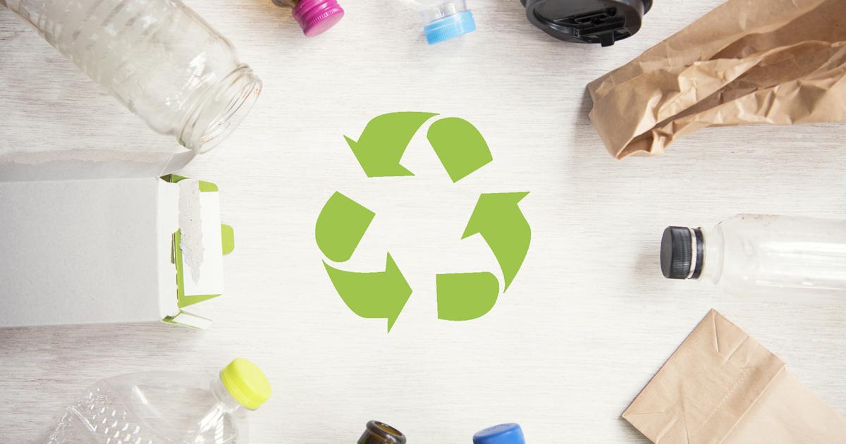 Déchets recyclables disposés autour du symbole du recyclage.