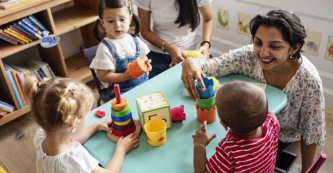 Enfants en crèches, jouant autour d'une table.