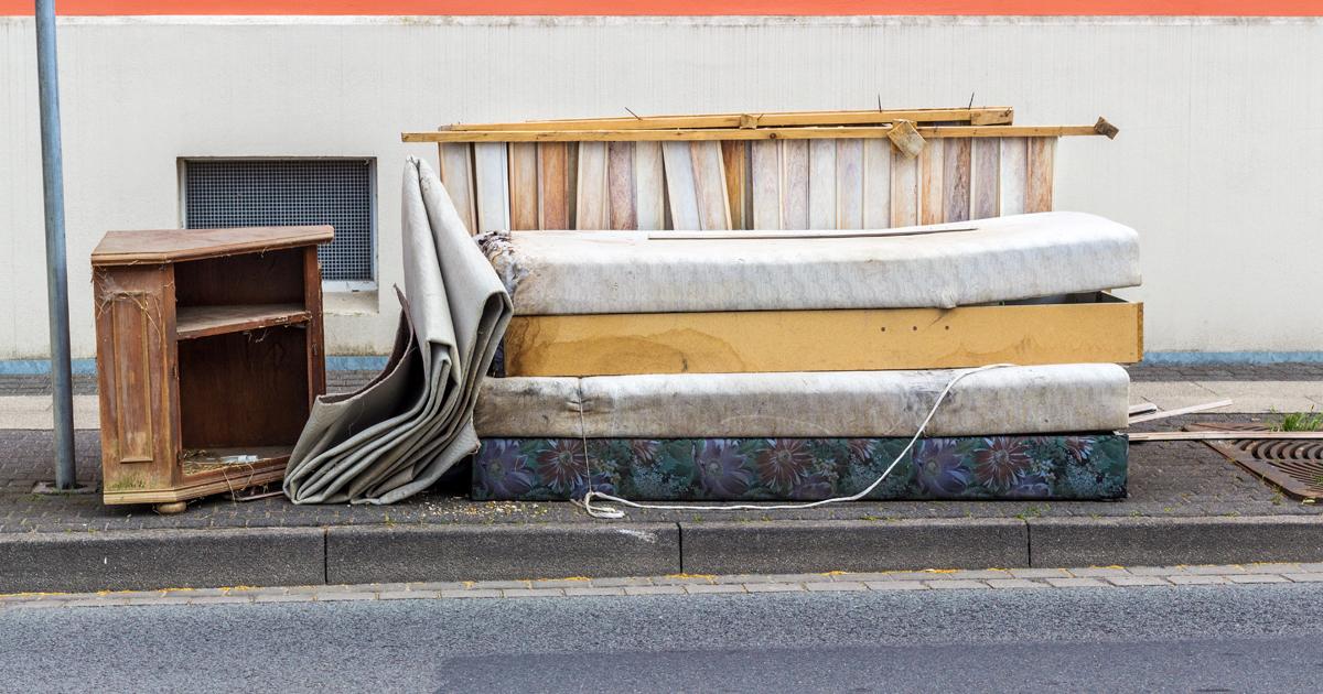 Vieux meubles et matelas sur un trottoir.