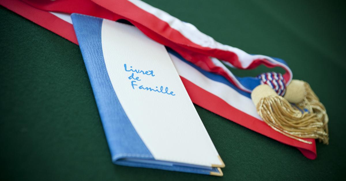 Livret de famille posé sur une table à côté d'une écharpe tricolore.