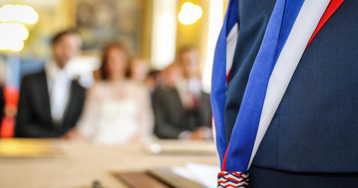 Personne élue ceinte de l'écharpe tricolore et vue de dos face à un couple.