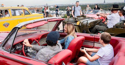 Personnes dans une voiture décapotable lors de l'évènement Suresnes auto retro.