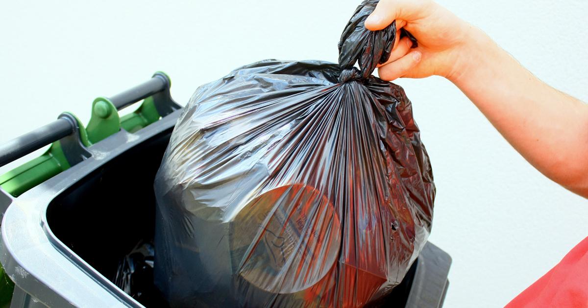 Personne qui place un sac poubelle dans un bac de collecte.