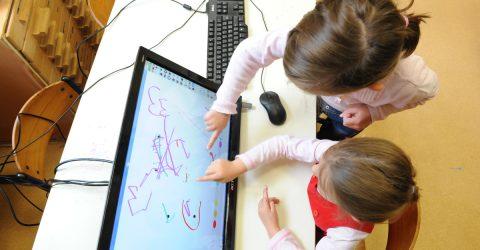 Élèves dessinant sur une tablette numérique.