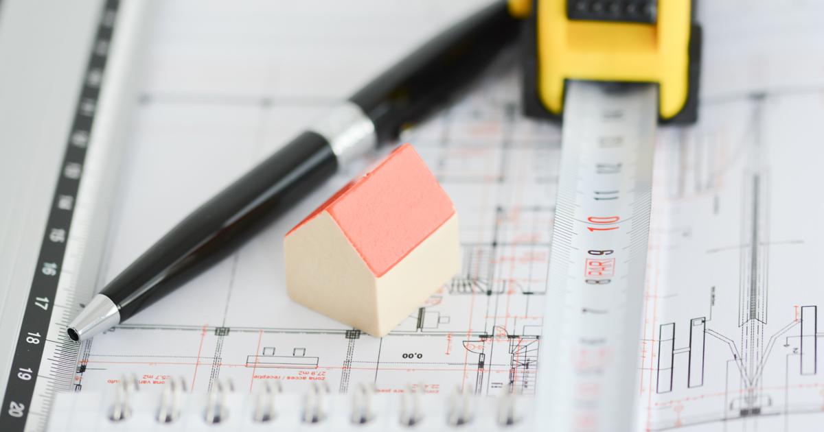 Plan de construction sur lequel sont posés un stylo, une maison miniature et un mètre déroulant.