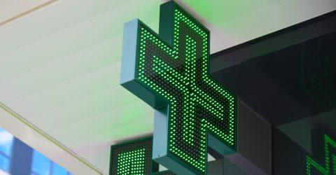 Croix verte sur la façade d'une pharmacie.