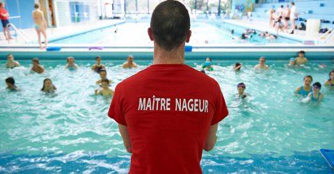 Vue d'un maître nageur de dos face aux deux bassins.