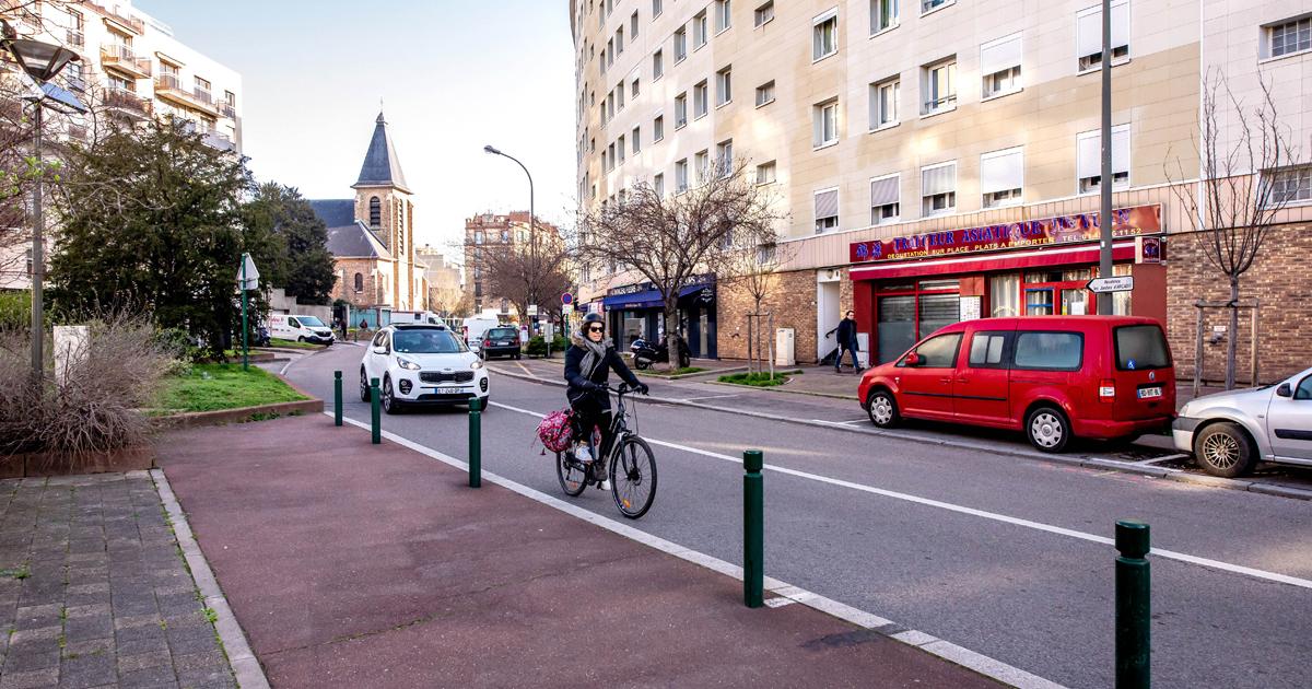Vue de la voie publique avec des véhicules qui circulent et des voitures garées.