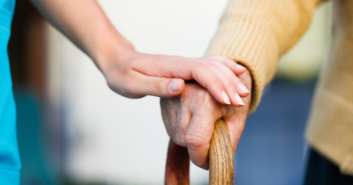 Main posée sur une main portant une canne.
