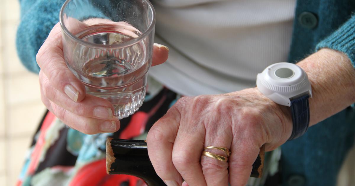 Personne âgée tenant un verre d'eau