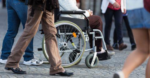 Personne en fauteuil dans la rue, entourée de passants.