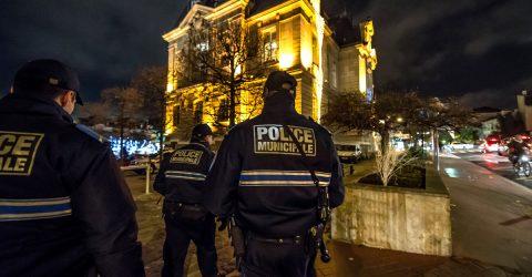 Policiers municipaux vus de dos devant l'hôtel de ville.