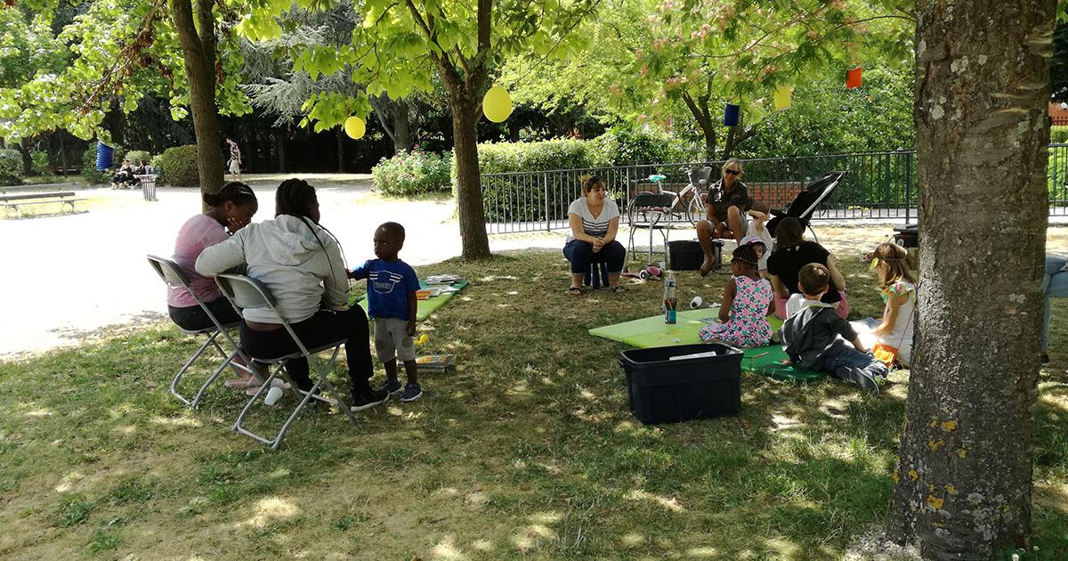 Groupe d'enfants et d'adultes assis dans l'herbe.