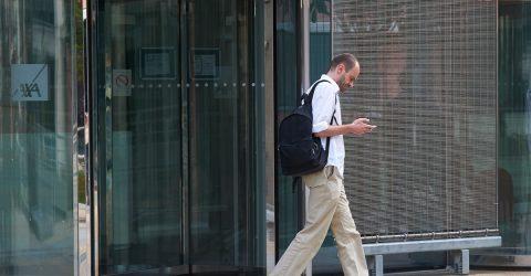 Salarié sortant de l'immeuble où il travaille.