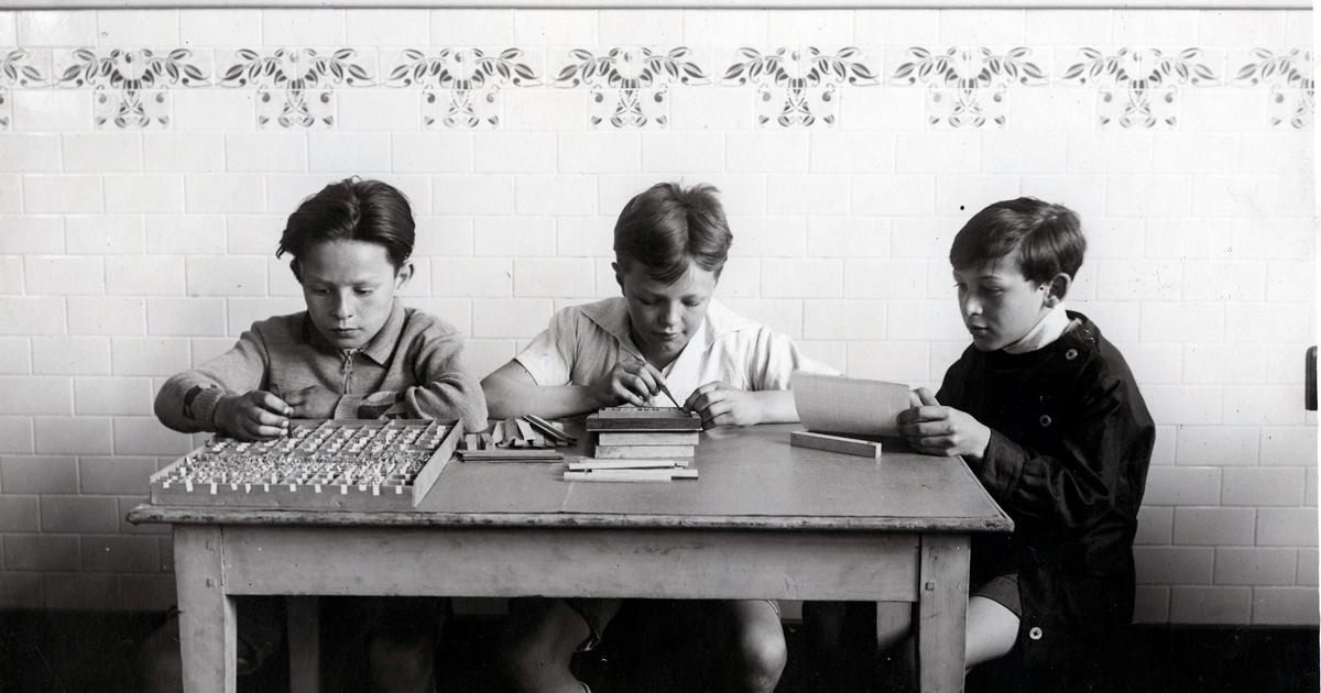 Photo historique présentant les élèves à un bureau