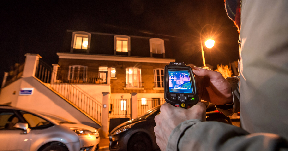 Agent prenant une photo thermique d'un logement